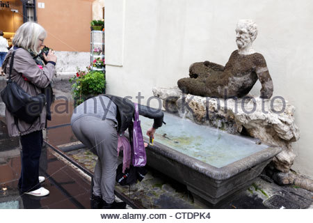 two female tourist trying to photograph an old sculpture in Rome Italy. - Stock Photo