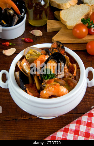 Cacciucco, Italian fish stew consisting of several different types of fish and shellfish cooked in wine, tomatoes - Stock Photo