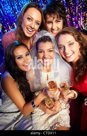 Group of friends drinking to the health and happiness of the bride - Stock Photo