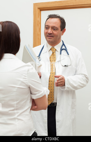 Doctor holding files while talking to a patient - Stock Photo