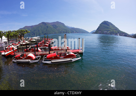 Pedalo boats on lake in Lugano with view of Monte San Salvador, Lake Lugano, Ticino, Switzerland, Europe - Stock Photo