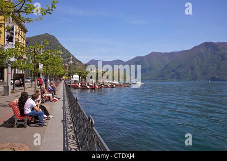 Visitors enjoying lakeside sunshine, city of Lugano, Lake Lugano, Ticino, Switzerland, Europe - Stock Photo