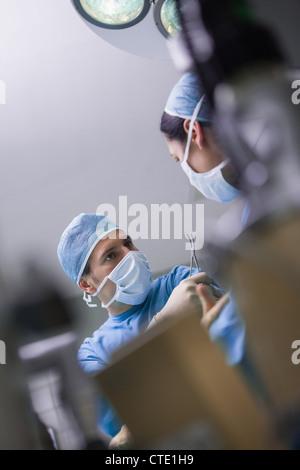 Serious doctor giving a surgical scissor to a nurse - Stock Photo