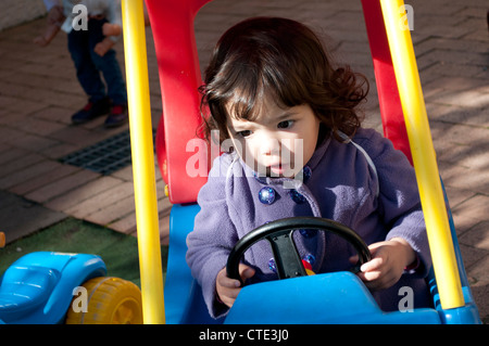 Little girl driving a toy car - Stock Photo