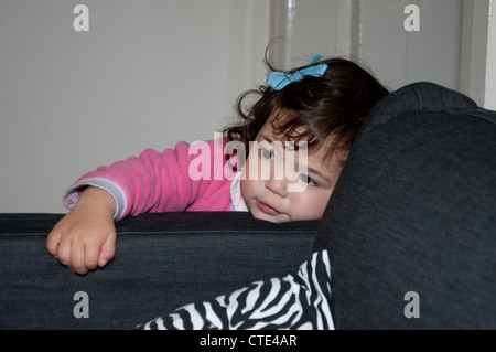 Little girl with blue bow leaning on a sofa - Stock Photo