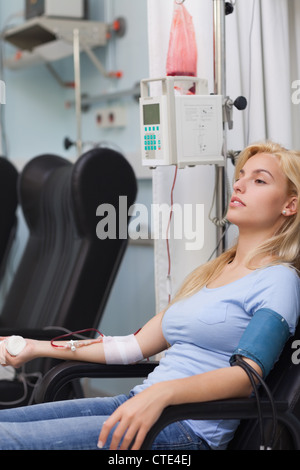 Blonde patient receiving a blood transfusion - Stock Photo