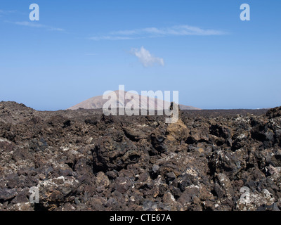 Lava-field with sharp uneven rocks and an old volcano in the background near Timanfaya in Lanzarote - Stock Photo
