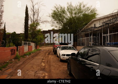 Razor wire surrounds residential properties located near the Mexican border wall in Nogales, Arizona, USA. - Stock Photo