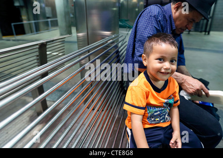 Hispanic boy with his grandfather on a subway platform in Boston, Massachusetts - Stock Photo