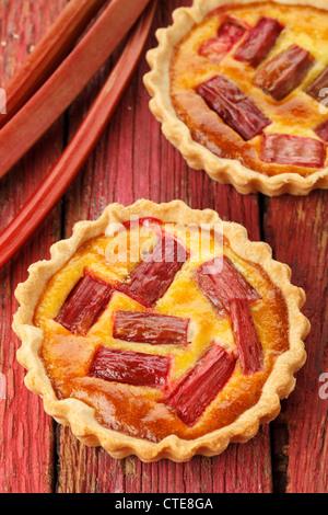 Rhubarb & saffron cream tart on a red wooden background - Stock Photo