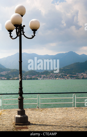 Lamp post and lake-side promenade in Pisogne with distant view of Lovere across Lago d'Iseo, mountains, clouds building. - Stock Photo