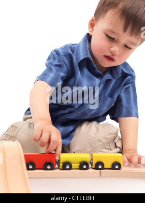 Two year old boy plaing with a wooden toy train on a railroad - Stock Photo