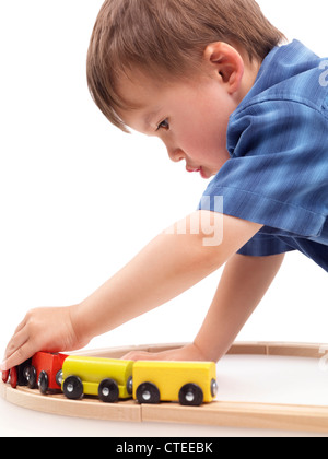 Two year old boy plaing with a wooden toy train on a railroad isolated on white background - Stock Photo