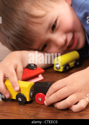 Happy two year old boy playing with a colorful toy train on hardwood floor - Stock Photo