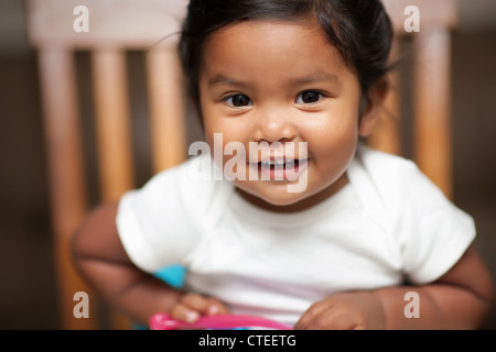 excited baby girl holding a spoon and sitting on a booster seat - Stock Photo
