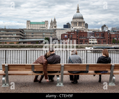 UK, London, South Bank, - July 2012 Tired tourists relax on a bench next to the River Thames in London - Stock Photo