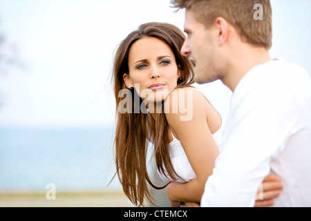 Portrait of an attractive woman seriously listening to her boyfriend while on a date - Stock Photo