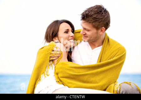 Portrait of a romantic couple embracing while wrapped with a blanket - Stock Photo
