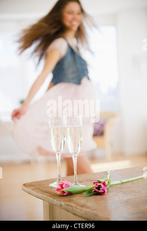USA, New Jersey, Jersey City, Champagne flutes on table, woman dancing in background - Stock Photo