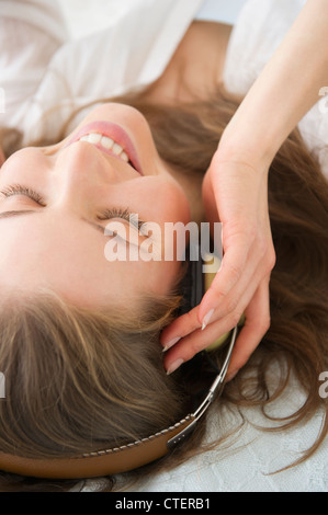 USA, New Jersey, Jersey City, Woman lying on bed and listening to the music - Stock Photo