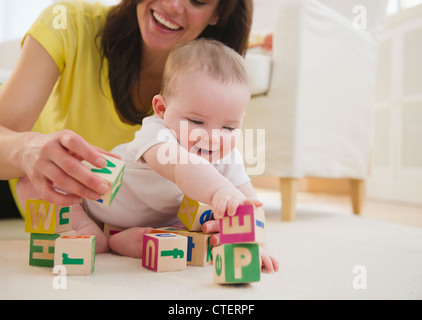 USA, New Jersey, Jersey City, Mother and baby daughter (6-11 months) playing with blocks - Stock Photo