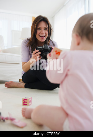 USA, New Jersey, Jersey City, Mother photographing baby daughter (6-11 months) - Stock Photo