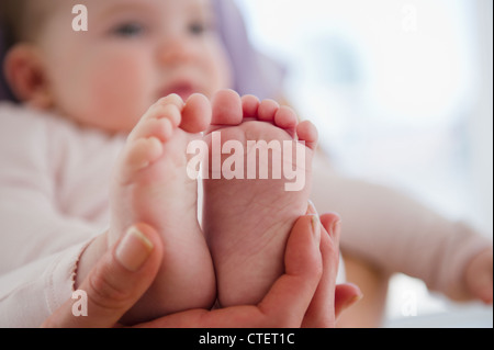 USA, New Jersey, Jersey City, Close up of mother's hand holding baby daughter's (6-11 months) feet - Stock Photo