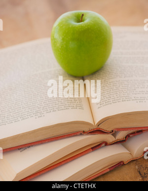 Close up of apple on open books, studio shot - Stock Photo