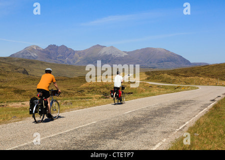 Two cyclists cycling on a quiet country road towards An Teallach in northwest highlands Dundonnell Wester Ross Ross - Stock Photo