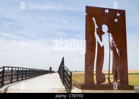Pilgrim walking Camino de Santiago near metal Camino de Santiago sculpture in Fromista, Palencia province, Spain - Stock Photo