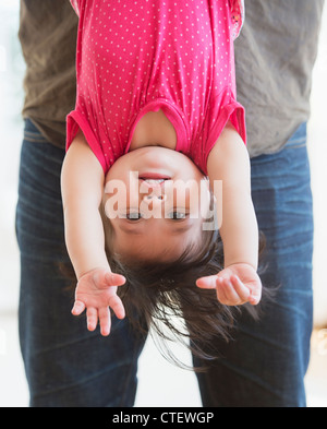 USA, New Jersey, Jersey City, Father holding baby daughter (12-17 months) upside down - Stock Photo