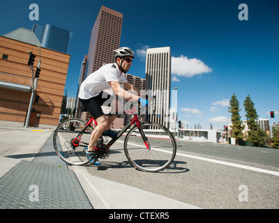 USA, California, Los Angeles, Young man road cycling on city street - Stock Photo
