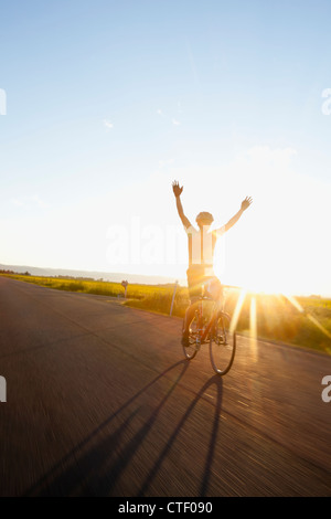 USA, Montana, Kalispell, Silhouette of cyclist holding arms up - Stock Photo