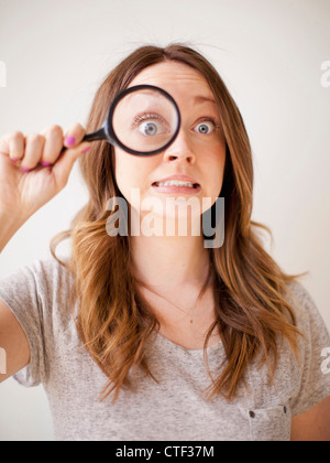 Young woman making a face while holding magnifying glass - Stock Photo