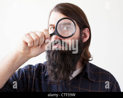 Bearded young man looking through magnifying glass - Stock Photo