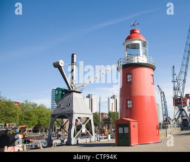 Historic cranes and red lighthouse in the Haven museum, Leuvehaven, Rotterdam, Netherlands - Stock Photo