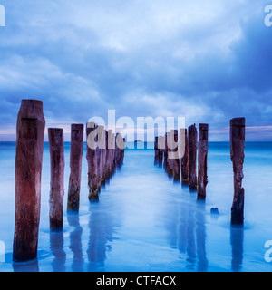 Storm clouds gather over old jetty posts. - Stock Photo