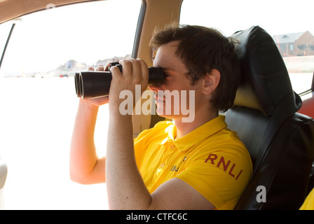 RNLI lifeguard surveying the coast through his binoculars - Stock Photo