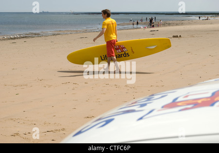 RNLI lifeguard walking towards sea with surf board - Stock Photo