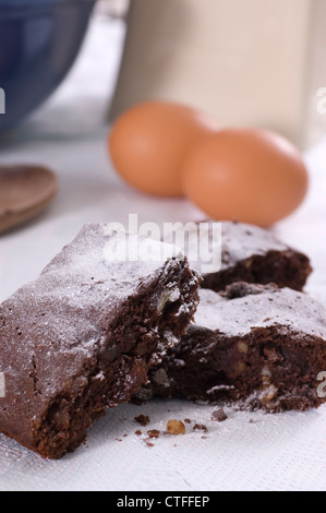 Pecan, Rum and Stem Ginger Chocolate Brownies dusted with icing sugar - Stock Photo