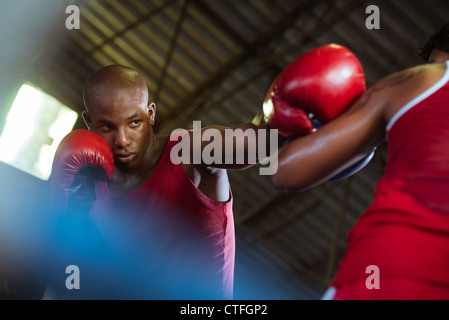 Sport and people, two men exercising and fighting in boxing gym - Stock Photo