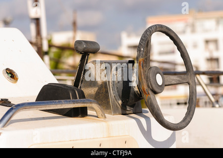 Old and worn steering wheel and throttle on a small fishing boat - Stock Photo