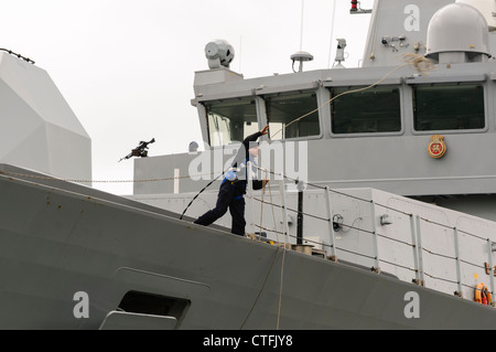 Sailor on Royal Navy Type 45 destroyer HMS Dragon throws a lead rope to dockers - Stock Photo