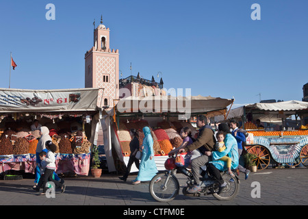 Morocco, Marrakech Square called Djemaa El Fna. Family on motorcycle in front of nuts and dry fruits sellers. - Stock Photo