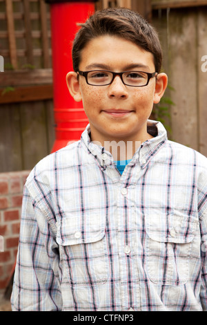 A young boy in glasses looking at the camera. - Stock Photo