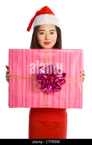 Attractive Chinese girl - Mrs Santa Claus, with very big gift box wrapped in pink paper and decorated by gigantic - Stock Photo