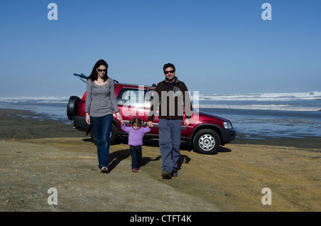 Family travels by four wheel drive vehicle on Ninety Mile Beach in Northland New Zealand. - Stock Photo