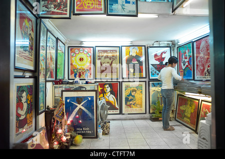 A two-story propaganda poster shop in Vietnam with people browsing through the posters. - Stock Photo