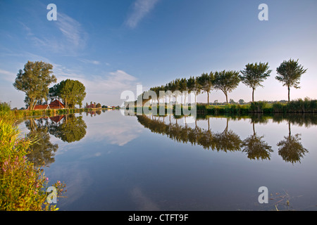 The Netherlands, Zuid Beemster, Beemster Polder, Farm behind dike of canal, which transports water to the sea. - Stock Photo