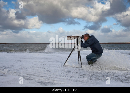 The Netherlands, IJmuiden, Photographer Frans Lemmens on pier during storm. - Stock Photo